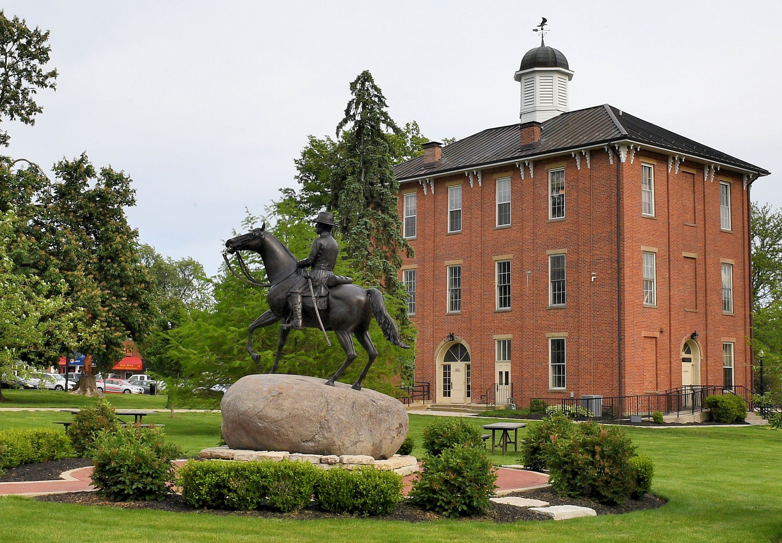 An outside view of town hall with a statue of a man on a horse and grounds